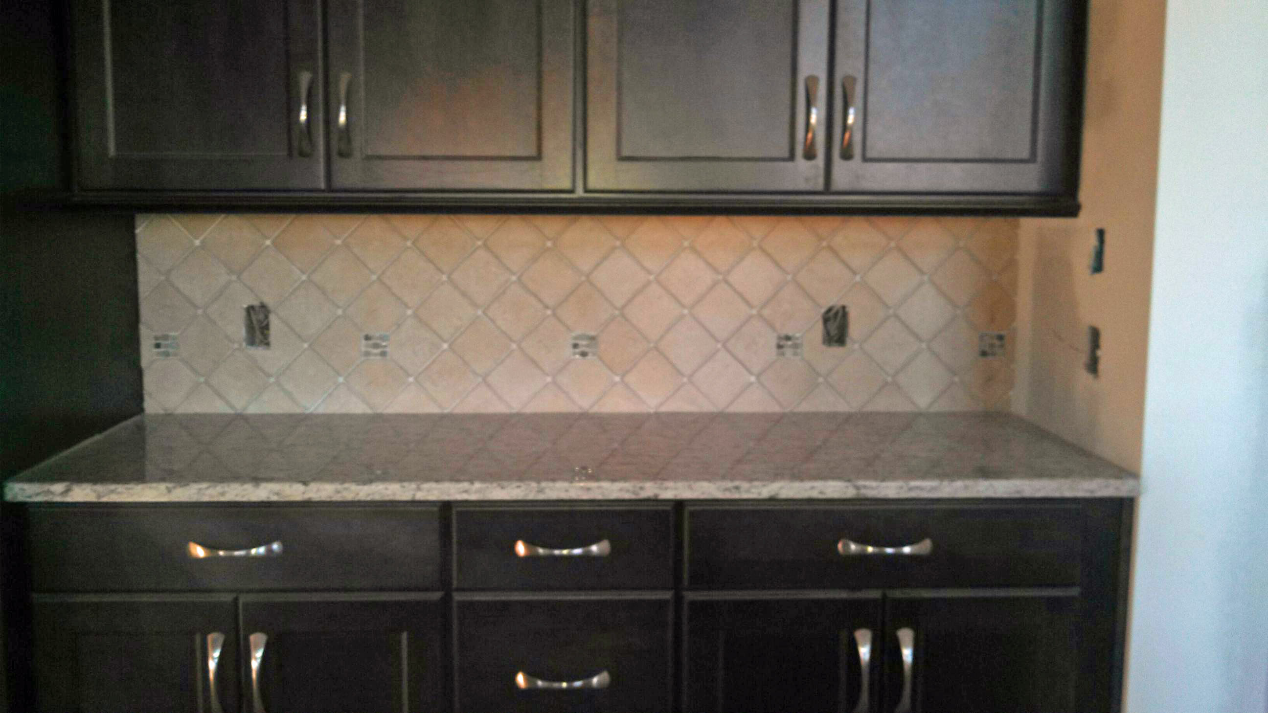 dark kitchen cabinets with blue backsplash